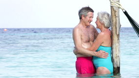 Senior Couple Embracing In The Sea Next To Hammock stock video