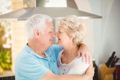 Senior couple embracing while touching nose in kitchen Stock Photos