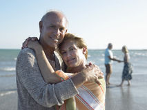Senior Couple Embracing On Tropical Beach. Portrait of romantic senior couple embracing with friends in background on tropical beach Stock Photo