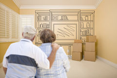 Senior Couple In Empty Room with Shelf Drawing on Wall Stock Photography