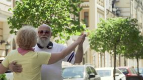 Senior couple enjoy each other and dancing waltz at urban street