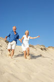 Senior Couple Enjoying Beach Holiday Running. Down Dune Stock Image