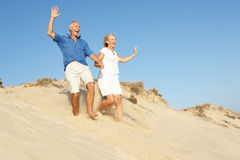 Senior Couple Enjoying Beach Holiday Running. Down Dune Stock Images