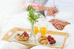 Senior couple enjoying breakfast in bed. Smiling Stock Photos