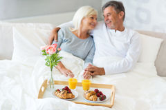 Senior couple enjoying breakfast in bed. Smiling Stock Photo