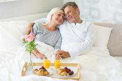 Senior couple enjoying breakfast in bed. Smiling Royalty Free Stock Images