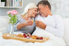 Senior couple enjoying breakfast in bed. Smiling Stock Image