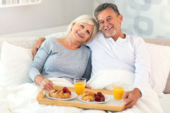 Senior couple enjoying breakfast in bed. Smiling Stock Photography