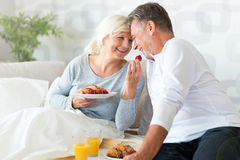 Senior couple enjoying breakfast in bed Royalty Free Stock Photos