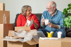 Senior Couple Sharing Chinese Food Surrounded By Moving Boxes royalty free stock photos