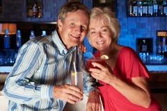 Senior Couple Enjoying Cocktail In Bar. Smiling To Camera stock photo
