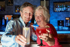 Senior Couple Enjoying Cocktail In Bar. Smiling To Camera stock photography