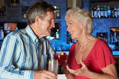 Senior Couple Enjoying Cocktail In Bar. Smiling To Camera royalty free stock photos