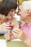 Senior Couple Enjoying Cocktails In Outdoor Bar Together Royalty Free Stock Images