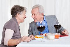 Senior couple enjoying dinner together. Portrait Of Senior Couple With Wine Glasses Sitting At A Restaurant Stock Image