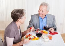Senior Couple Enjoying Dinner Together. Portrait Of Senior Couple With Wine Glasses Sitting At A Restaurant Stock Photo