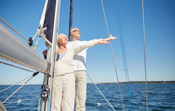 Senior couple enjoying freedom on sail boat in sea Stock Photography