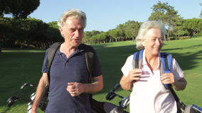 Senior Couple Enjoying Game Of Golf. Senior couple carrying golf clubs walk along fairway towards camera talking.Shot on Canon 5d Mk2 with a frame rate of 30fps stock video footage