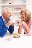 Senior Couple Enjoying Hot Drink In Kitchen Stock Photography