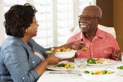 Senior Couple Enjoying Meal At Home Stock Photo