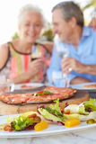 Senior Couple Enjoying Meal In Outdoor Restaurant Royalty Free Stock Image