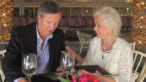 Senior Couple Enjoying Meal In Restaurant Royalty Free Stock Photos