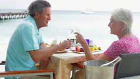 Senior Couple Enjoying Meal In Seafront Restaurant. Senior couple enjoying meal at waterfront restaurant - woman offers man piece of fruit to try.Shot on Canon stock video footage