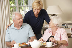 Senior Couple Enjoying Meal Together At Home With Home Help Stock Photography