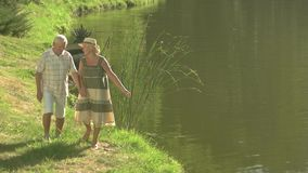 Senior couple enjoying nature near water.