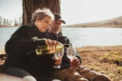 Senior couple enjoying outdoors camping near a lake Stock Photos