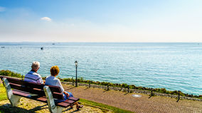 Senior couple enjoying a rest and view of the inland sea named IJselmeer with its wind farms. From the historic fishing village of Urk in the Netherlands Royalty Free Stock Photos