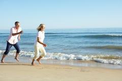 Senior Couple Enjoying Romantic Beach Holiday. Running Royalty Free Stock Photos