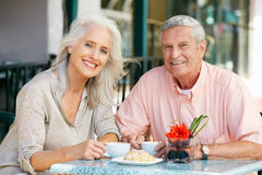 Senior Couple Enjoying Snack At Outdoor Cafe Stock Photography
