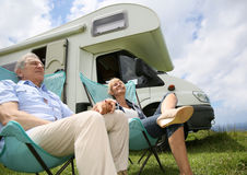 Senior couple enjoying sunny day in camping chairs Royalty Free Stock Images