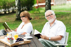 Senior couple enjoying themselves outdoors. Senior couple reading books in the garden, shallow depth of field Royalty Free Stock Images