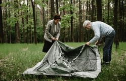 Happy senior family enjoying spending time together. Senior couple enjoying vacation and is setting up the tent. Adults spending summer holiday on nature and stock photo