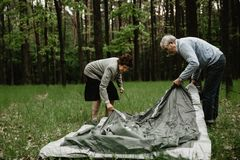 Happy senior family enjoying spending time together. Senior couple enjoying vacation and is setting up the tent. Adults spending summer holiday on nature and stock images