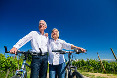 Senior couple enjoying view on bike trip. Women and men leaning against each other stock photography