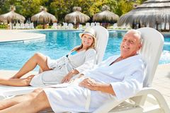 Senior couple enjoys the luxury summer vacation by the pool. Of the Spa Hotel royalty free stock images