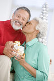 Senior Couple Exchanging A Christmas Gift Royalty Free Stock Photos