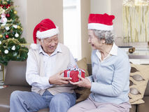 Senior couple exchanging christmas gifts. Asian senior couple with Christmas hats exchanging gifts Royalty Free Stock Images