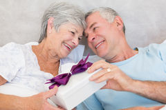 Senior couple exchanging gift box in bed Royalty Free Stock Images