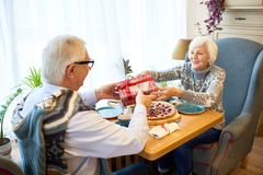 Senior Couple Exchanging Gifts. Portrait of happy senior couple enjoying Christmas holidays together, exchanging gifts sitting  table in cafe Stock Photo