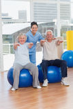 Senior couple on exercis ball with trainer Stock Images
