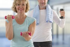 Senior couple exercise together at home doing aerobics lift up dubbells smiling stock photo