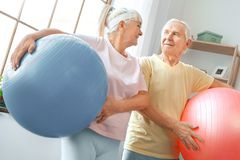 Senior couple exercise together at home health care carry balls looking on each other. Senior men and women exercise together indoors carry exercise balls Royalty Free Stock Images