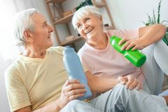 Senior couple exercise together at home health care drinking water refreshment. Senior men and women exercise together indoors rest drinking water talking Royalty Free Stock Image
