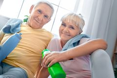 Senior couple exercise together at home health care drinking water. Senior men and women exercise together indoors rest drinking water looking camera smiling Stock Image