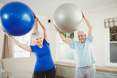 Senior couple exercising with exercise ball. Senior couple lifting exercise ball while exercising Stock Image
