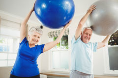 Senior couple exercising with exercise ball. Senior couple lifting exercise ball while exercising Royalty Free Stock Images